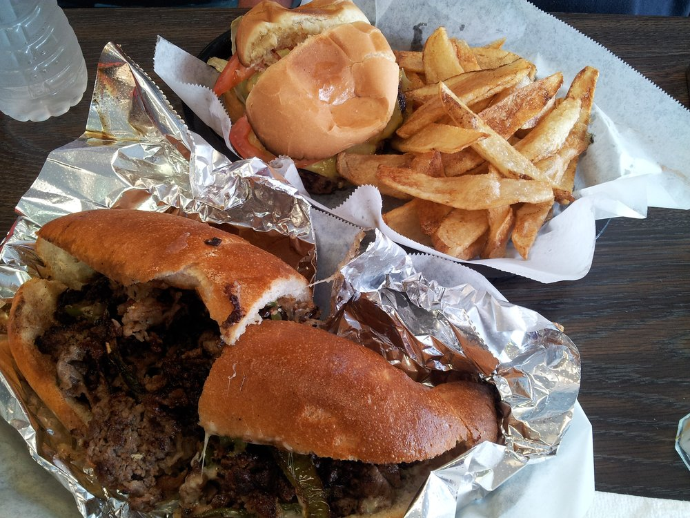 Lots of philly cheese steak stuffed toasted bun wrapped in foil with thick, hand cut fries from Mo's Best Eatery in Arlington, Texas.