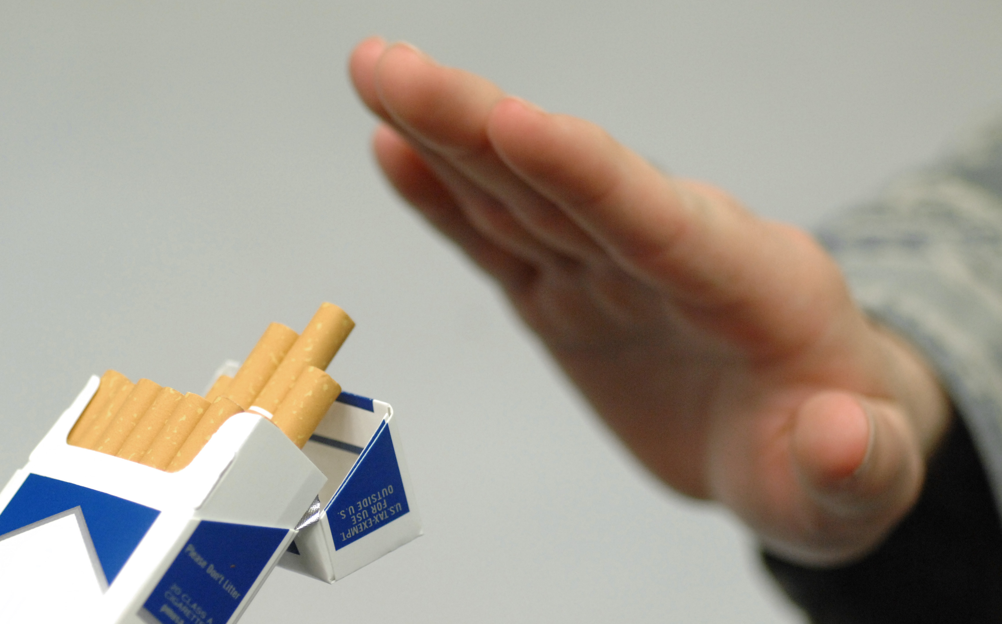 man holding up a hand to offered pack of cigarettes. Quit smoking in 2016.