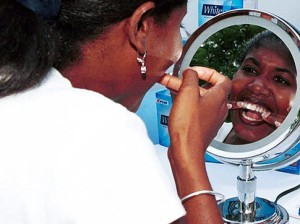 Women placing whitening strips on her teeth in front of a mirror.